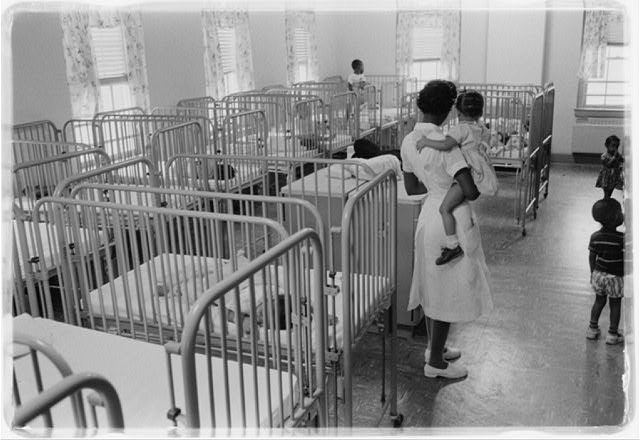 [A woman holding a child in the nursery at Junior Village, Washington, D.C.]