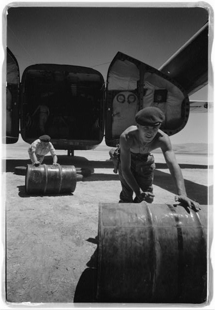 [Jordanian military guards unloading barrels of oil at Jerusalem Airport in Jordan]