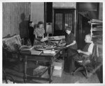 [Interior of L.C. Handy Studio, 494 Maryland Ave., SW, Washington, D.C., with Handy's daughters, Mrs. Mary Evans and Mrs. Alice Cox, and Mr. Edgar Cox (left to right) looking at prints dating back to Mathew Brady piled on table]