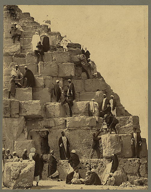 [Several people gathered at the base of the Great Pyramid, others climbing]