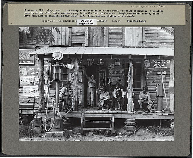 Country store on dirt road. Sunday afternoon. Note the kerosene pump on the right and the gasoline pump on the left. Rough, unfinished timber posts have been used as supports for porch roof.  Negro men are sitting on the porch. Brother of store owner stands in doorway. Gordonton, North Carolina