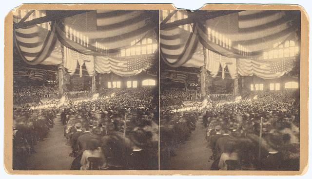 [Interior view of a large convention hall filled with people sitting in chairs]