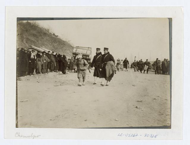 [A Korean coolie carrying medical supplies from shore to hospital at Chemulpo]