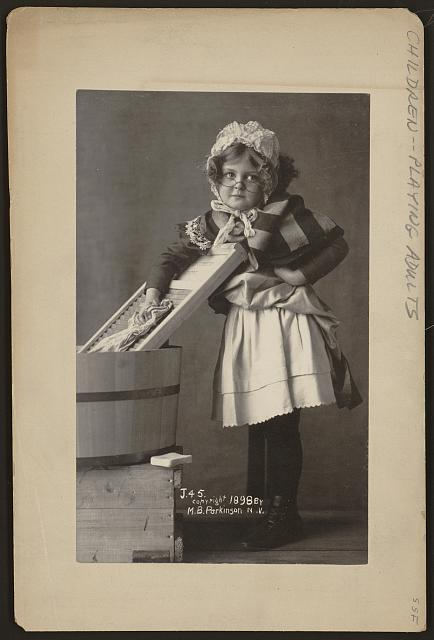 [Girl wearing eyeglasses, bonnet and apron, with washboard and tub]