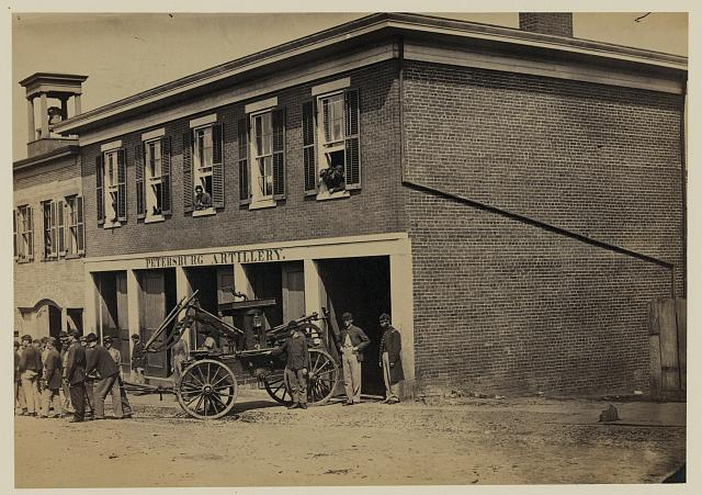 [Union soldiers pull a fire engine from a garage designated Petersburg artillery]