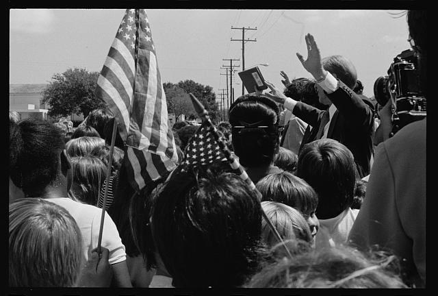 [President Gerald Ford greets flag-waving supporters at a campaign stop in the South]