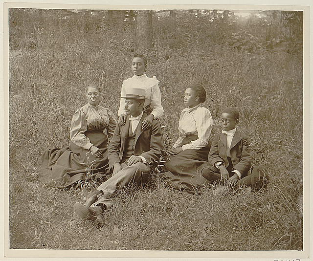 [African American family posed for portrait seated on lawn]