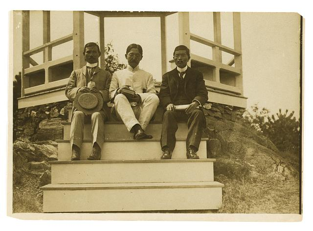 [Three Japanese men, possibly journalists, seated on the steps of a gazebo]