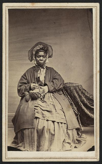 [Full-length portrait of an African American woman holding a basket]