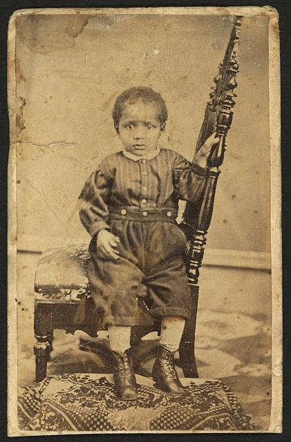 [Full-length portrait of an African American toddler seated on a chair]