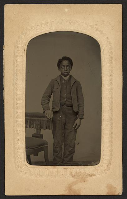 [Full-length portrait of an African American boy standing beside a chair]
