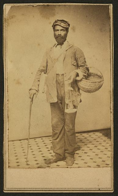 [Full-length portrait of an African American man with a basket and a cane, standing, facing front]