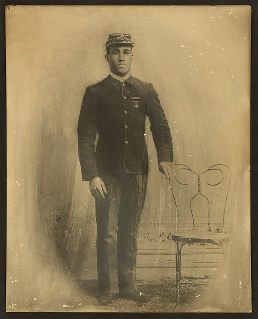 [Unidentified African American soldier, 9th cavalry, full-length portrait, standing, facing front, wearing uniform with marksman badge and sharpshooters medal, and kepi with crossed sabers]