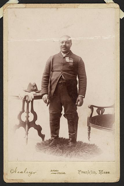 [Full-length portrait of an African American veteran and GAR member, standing on rug between table and chair]