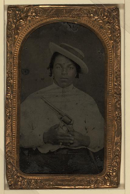[Black man, civilian, holding colt army revolver, ring on pinky finger, dred locks]