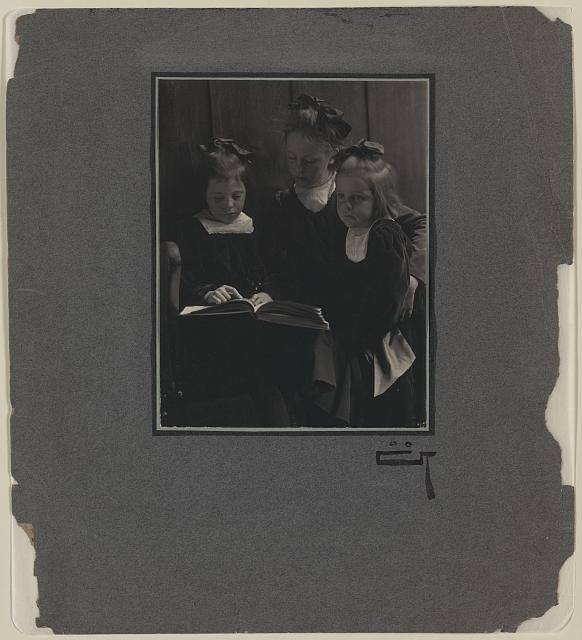 [Three young girls reading a book]