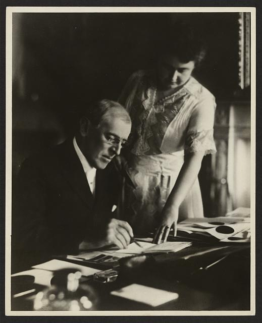 [President Woodrow Wilson, seated at desk with his wife, Edith Bolling Galt, standing at his side]