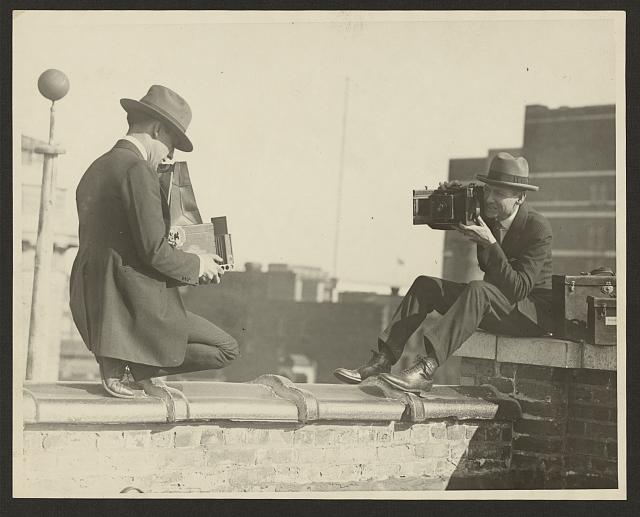 [Two photographers taking each other's picture with hand-held cameras while perched on a roof]