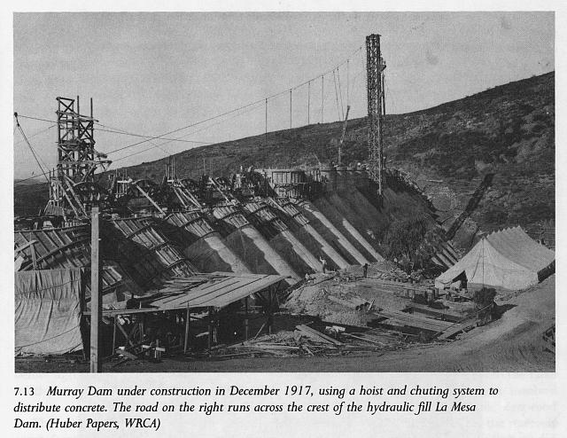 Murray Dam under construction in December 1917, using a hoist and chuting system to distribute concrete. The road on the right runs across the crest of the hydraulic fill La Mesa Dam (Huber Papers, WRCA)