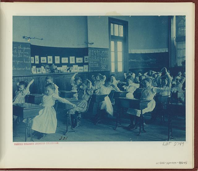 [Children doing calisthenics while sitting at their desks in a classroom, 5th Division public schools, Washington, D.C.]