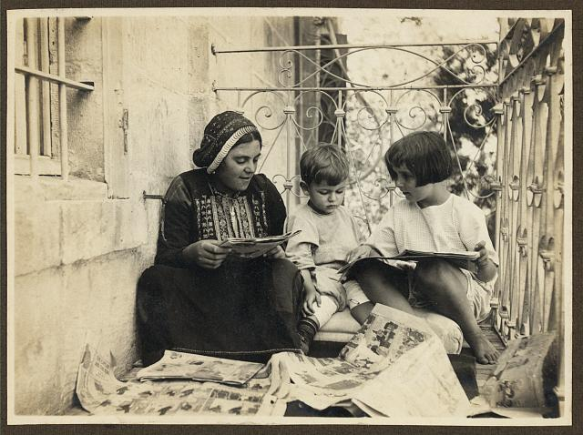 [Arab woman in traditional dress, seated with boy and girl (possibly members of the American Colony), looking at comics]