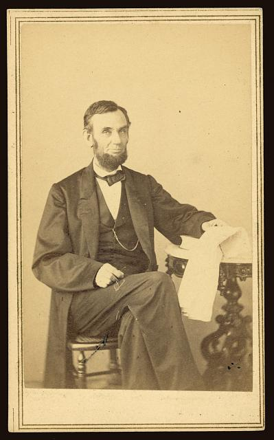 [Abraham Lincoln, U.S. President. Seated portrait, holding glasses and newspaper, Aug. 9, 1863]
