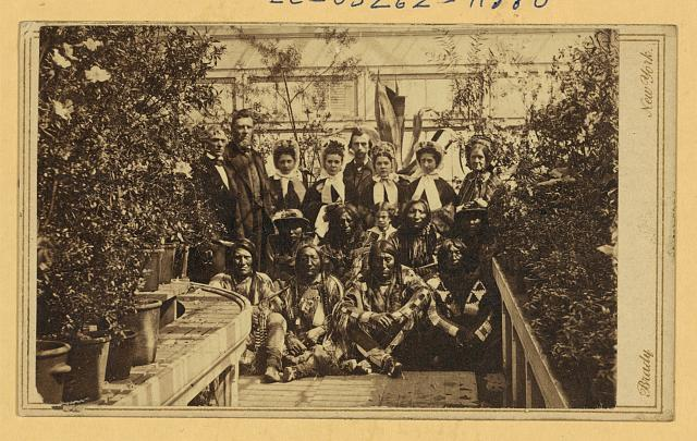 [Indian delegation in the White House Conservatory during the Civil War, with J.G. Nicolay, President Abraham Lincoln's secretary, standing in center back row and interpreter John Simpson Smith at back left]