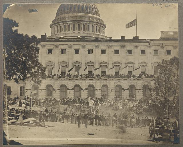 "[Washington, D.C. Spectators at side of the Capitol, which is hung with crepe and has flag at half-mast during the ""grand review"" of the Union Army]"