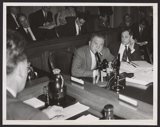 [Lionel Stander, with cigarette hanging from his lips, testifying before the House Un-American Activities Committee; attorney Leonard Boudin is sitting next to him]