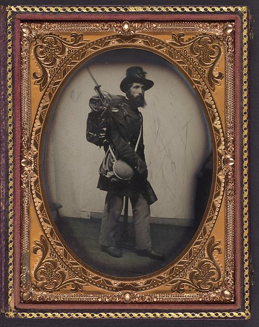 [Private Albert H. Davis of Co. E, 9th New Hampshire Infantry Regiment in uniform, shoulder scales, and Hardee hat with Model 1841 Mississippi rifle, sword bayonet, knapsack with bedroll, canteen, and haversack]