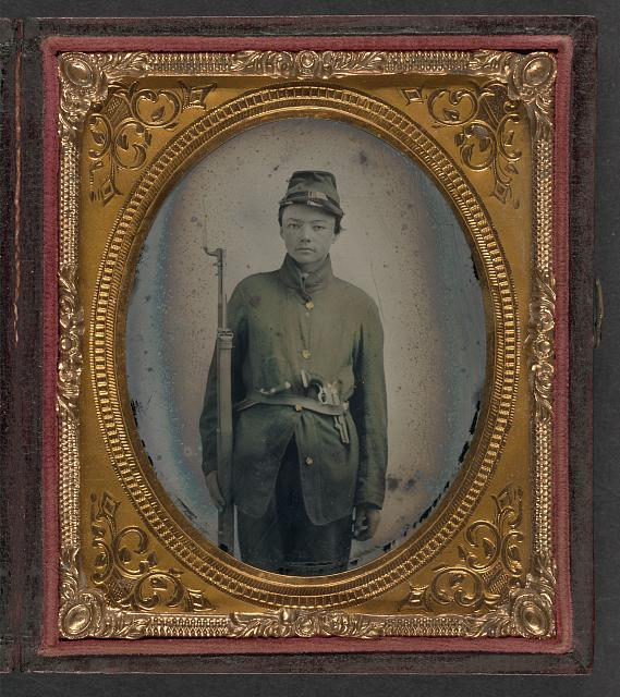 [Unidentified young soldier in Union uniform with bayoneted musket, knife, and revolver]