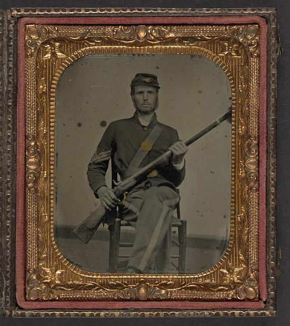 [Unidentified soldier in Union sergeant's uniform sitting on a chair and holding a musket]