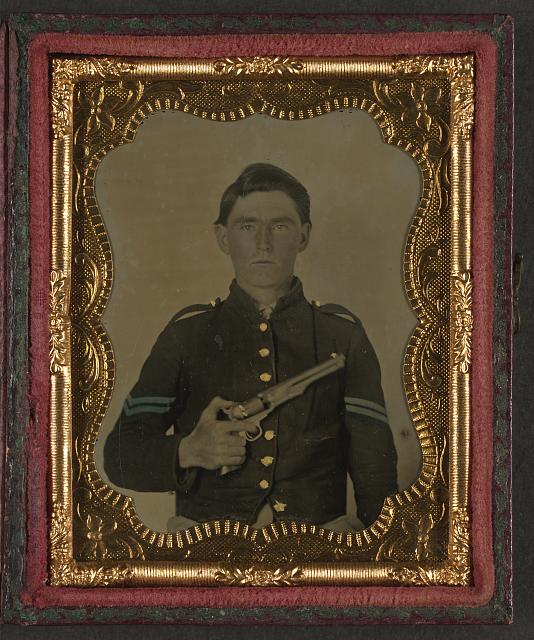 [Unidentified soldier in Union corporal's uniform holding Colt revolver to chest]