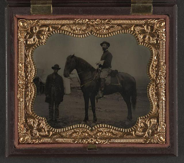 [Two unidentified soldiers in Union uniforms; African American soldier on left in frock coat and slouch hat; soldier on right sitting on horse and wearing shell jacket and slouch hat]