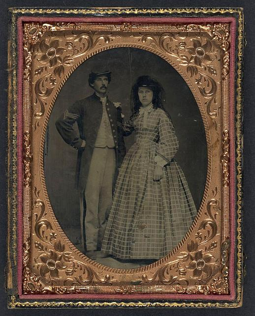 [Unidentified soldier in Union sergeant's frock coat and forage cap with unidentified woman in dress and hat with veil]