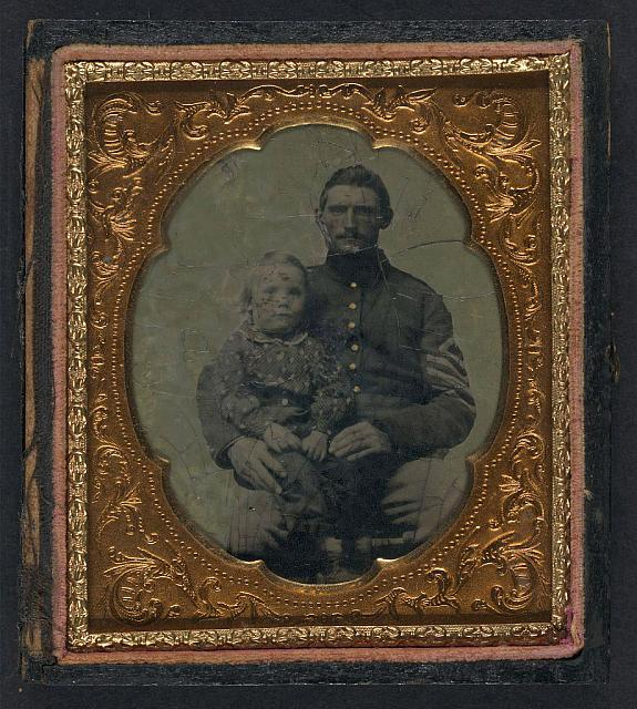 [Unidentified soldier in Union first sergeant's uniform with small child on lap]
