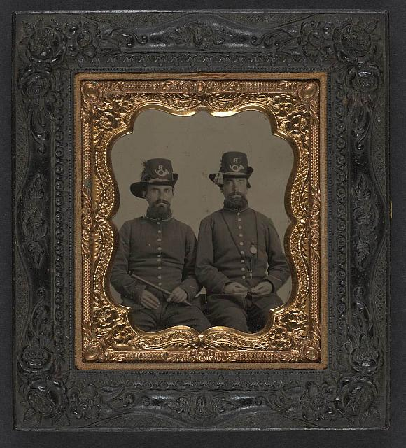 [Unidentified soldiers in Union uniforms and infantry Company B Hardee hats; soldier on left holds fife and soldier on right wears locket and key around his neck]