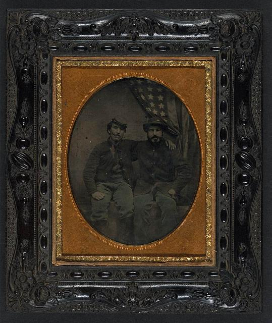 [Two unidentified soldiers in Union uniforms with cigars in mouths in front of American flag, one in 6th Army of the Potomac forage hat]