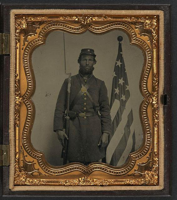 [Unidentified soldier in Union uniform and Company H cap with bayoneted musket, cap box, and Volunteer Maine Militia (VMM) belt buckle in front of American flag]