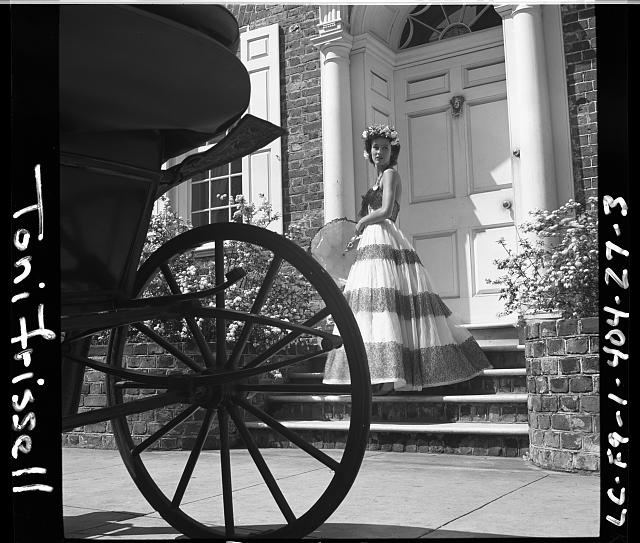 [Mrs. Stanley Mortimer posing in an evening gown, with parasol, on the steps of a house in Charleston, South Carolina, with the silhouette of a carriage wheel in the foreground]