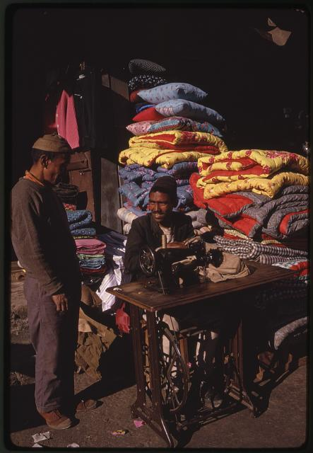 [Man with foot treadle sewing machine and pile of quilts behind him, Gangtok Bazaar, Sikkim]