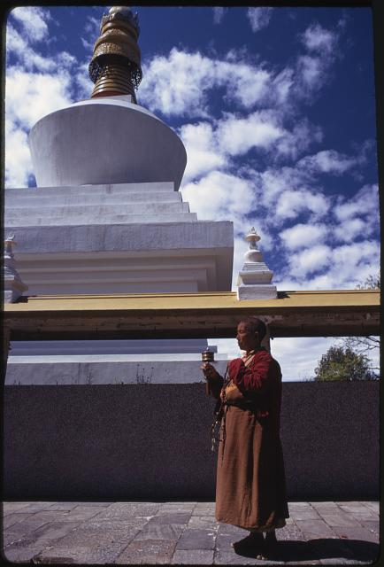 "Religious reliquary ""stupa"", woman turns prayer wheel in front of the Do-Drul Chorten stupa"