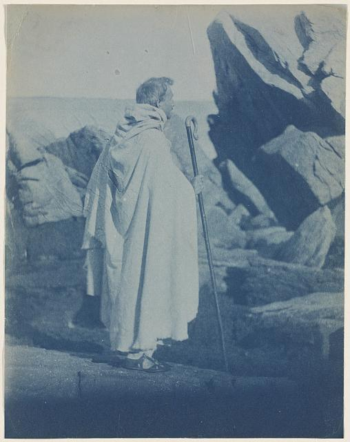 [F. Holland Day in cape with shepherd's crook next to rocks]