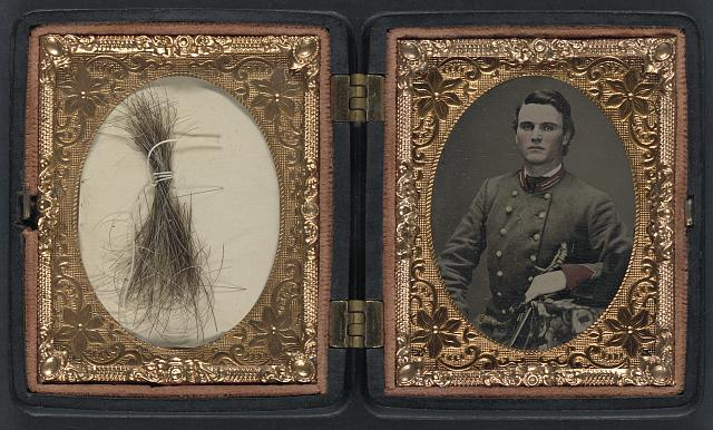 [Unidentified soldier in Confederate artillery first lieutenant's uniform holding sword, with lock of hair in case]