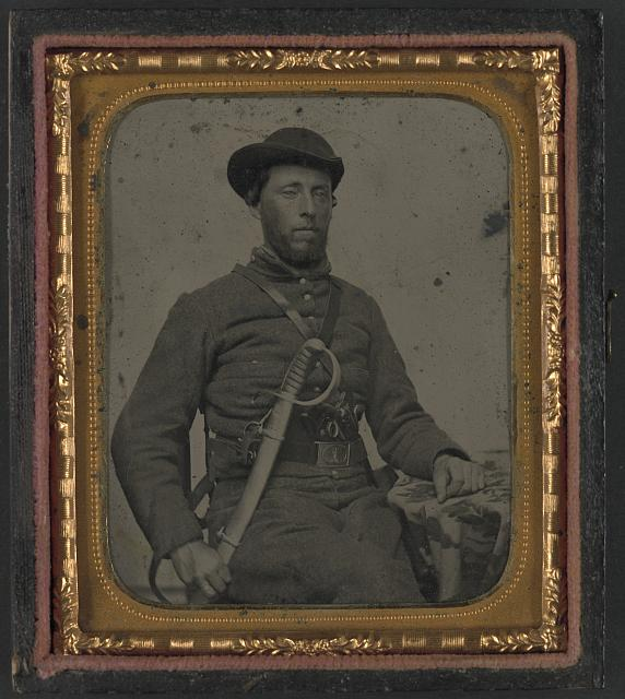 [Unidentified soldier in Confederate uniform and Virginia sword belt plate with revolver and cavalry sword]