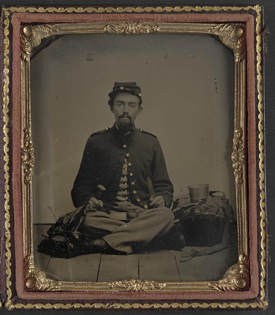 [Unidentified soldier in Union uniform with fork, knife, plate, and cup sitting on the floor and preparing to eat a slice of the apple on his lap]