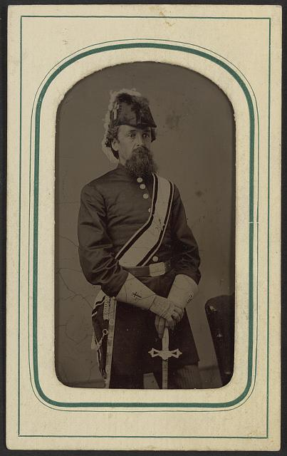 [Unidentified man in Masonic regalia including gauntlets, belt, sash, and Knights Templar hat with sword]