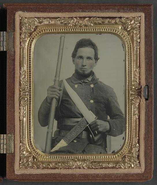 [Unidentified soldier in Confederate uniform with musket, D guard Bowie knife, and engraved knife sheath]