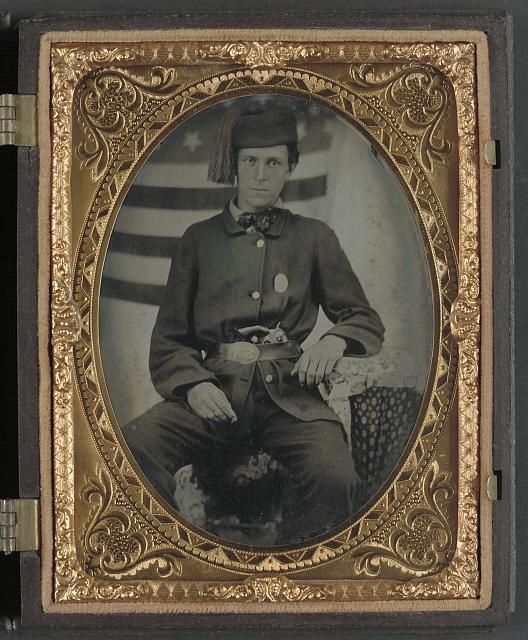 [Sergeant Albert S. Brownson of Company G, 12th Indiana Infantry Regiment, and Company D, 5th Indiana Cavalry Regiment, in uniform and upside down U.S. belt buckle with revolver in front of American flag backdrop]