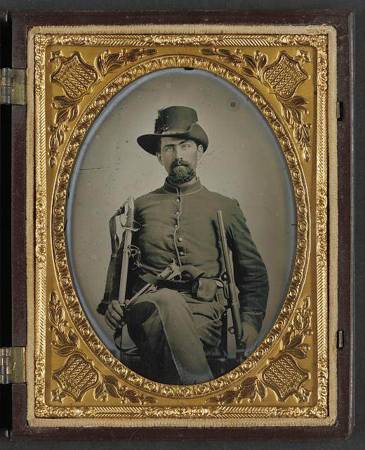 [Unidentified soldier in Union cavalry uniform with cavalry sword, Colt Army revolver, and carbine]